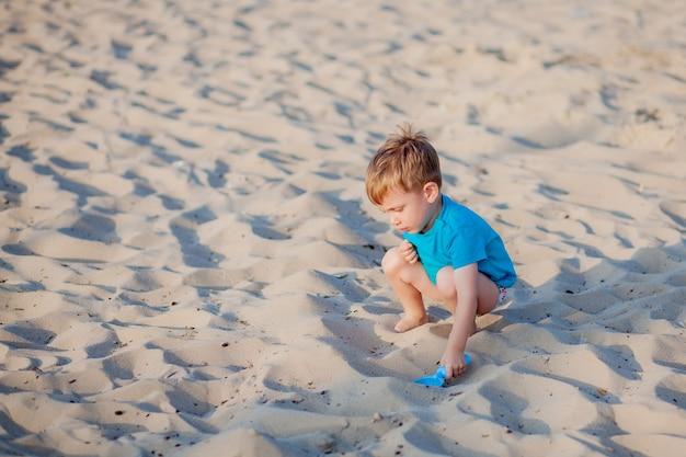 Jongen spelen op het strand kind spelen op zee in de zomer familie vakantie zand en water speelgoed bescherming tegen de zon