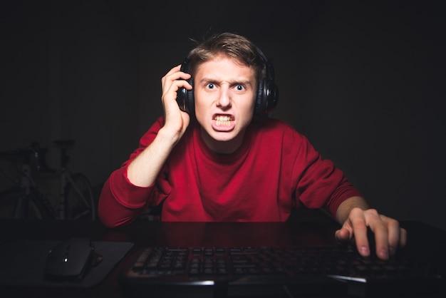 Jongen spelen van videogames op computer thuis, slecht uitziende computerscherm