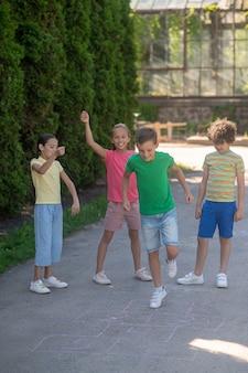 Jongen springen met opgeheven been en vrolijke vrienden