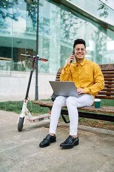 Jongen studeert in een park met een laptop en een scooter