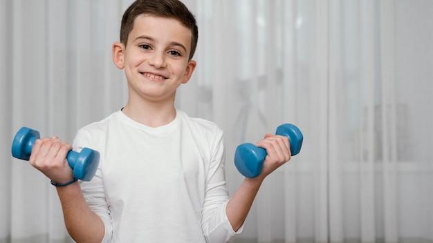Jongen tillen halters training oefeningen