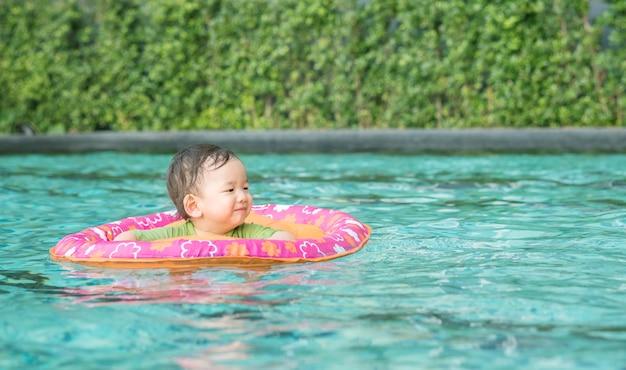 Jongen van de close-up zit de aziatische baby in een boot voor kinderen op de zwembadachtergrond met glimlachgezicht in gelukkige emotie