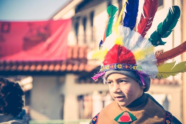 Jongen verkleed als een indiaanse indiaan toont grimassen. - afbeelding