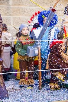 Jongen verkleed als een indiaanse indiaan toont grimassen. - jongen speelt met confettikanon