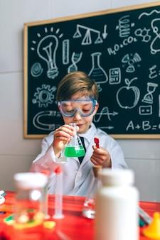 Jongen verkleed als scheikundige spelen met scheikundespel voor een schoolbord met tekeningen