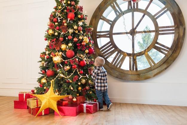 Jongen verkleedt een kerstboom