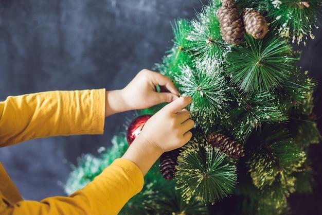 Jongen versieren de kerstboom met ballen en dennenappels