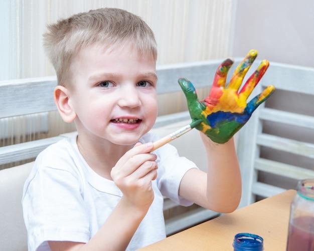 Jongen versiert zijn handen met verschillende kleuren