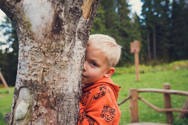 Jongen verstopt zich achter een boomstam