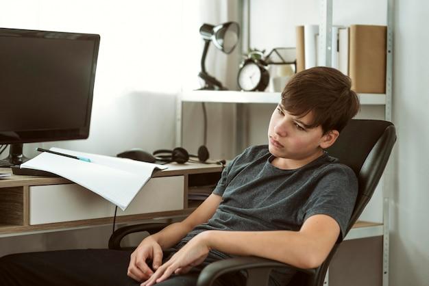 Jongen verveelt zich over huiswerk