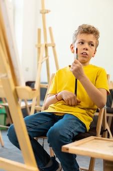 Jongen verveelt zich tijdens de kunstles op school