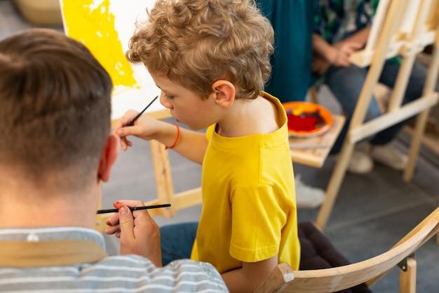 Jongen voelt zich goed schilderen met aquarel in de buurt van leraar
