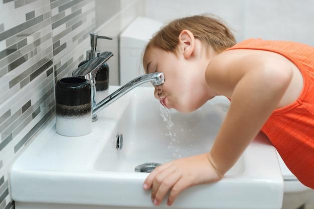 Jongen wassen gezicht in de badkamer. ochtend hygiëne. preteen jongen wordt gewassen in een wastafel. gezonde kindertijd en levensstijl. elke dag mondhygiëne. gezondheidszorg, kindertijd en mondhygiëne.