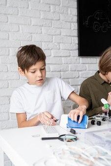 Jongen werkt met led-verlichting op experimenteel bord voor wetenschappelijk project met vergrootglas