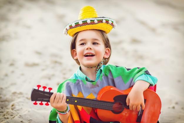 Jongen zijn gitaar spelen op het strand