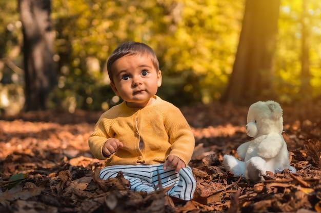 Jongen zit in de bladeren van de bomen met een witte teddybeer in het park op een herfstzonsondergang. natuurlijke verlichting