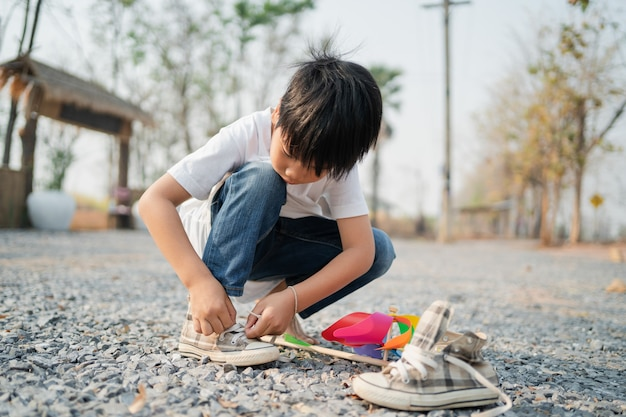 Jongen zit in een park met schoenveters
