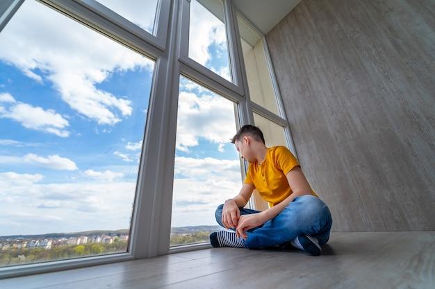 Jongen zit op de vloer op het balkon. kid kijken naar de natuur buiten raam. isolatie thuis tijdens quarantaine. trieste jongen dromen.