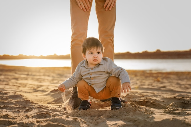 Jongen zit op de voeten van zijn vader in het zand op de rivieroever.