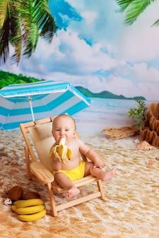 Jongen zit op een ligstoel, zonnebaadt op een zandstrand met palmbomen aan zee en eet een banaan