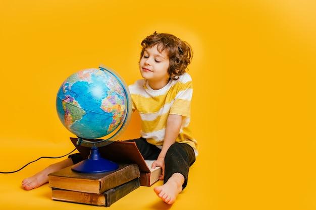 Jongen zit op een stapel boeken, vlakbij de globus