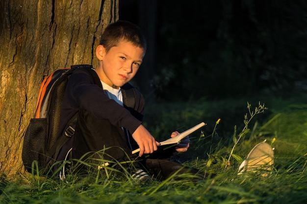 Jongen zittend onder een boom leest een boek. schoolgaande kind leert in de natuur.