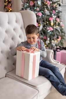 Jongen zittend op de bank en probeert zijn geschenk uit te pakken