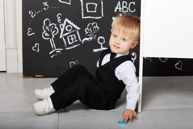 Jongen zittend op de vloer met schoolbord