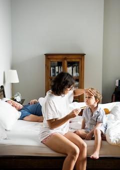 Jongen zittend op het bed en zijn moeder temperatuur controleren