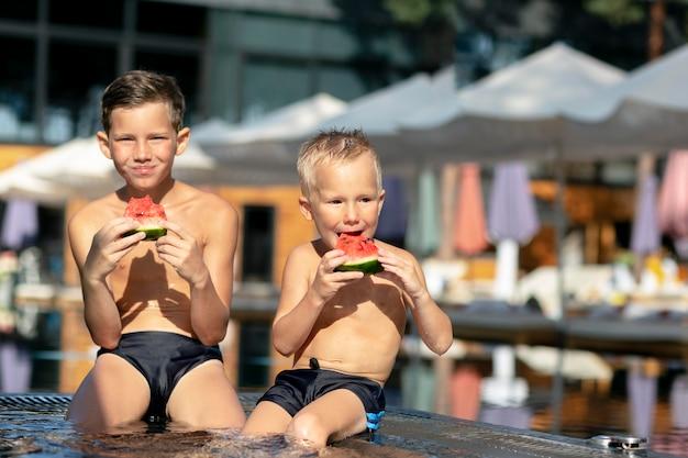 Jongens bij het zwembad met watermeloen