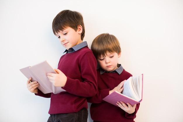 Jongens die een boek in studio lezen.
