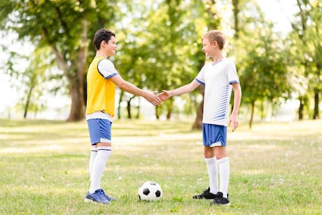 Jongens die handen schudden voor een voetbalwedstrijd