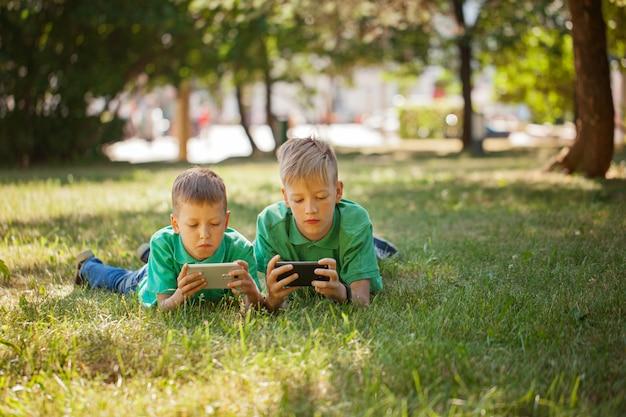 Jongens die samen spelletjes spelen op telefoons
