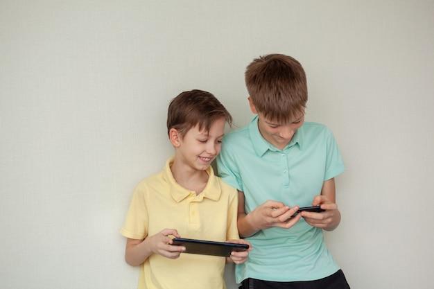 Jongens die thuis spelletjes spelen op mobiele telefoons