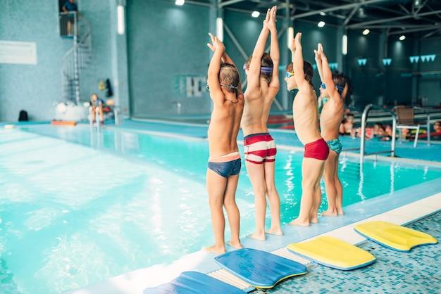 Jongens doen sportieve oefeningen met de handen omhoog