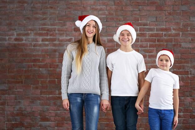 Jongens en meisje in kerstmutsen op een rij op bakstenen muurachtergrond
