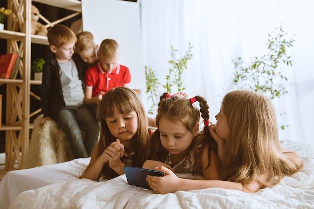 Jongens en meisjes die thuis verschillende gadgets gebruiken. childs met slimme horloges, smartphone en koptelefoon. selfie maken, chatten, gamen, video's kijken. interactie van kinderen en moderne technologieën.
