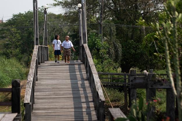 Jongens en meisjes lopen over de brug om naar school te gaan, landelijk woonconcept.
