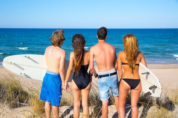 Jongens en meisjes tienersurfers achteraanzicht op zoek naar strand
