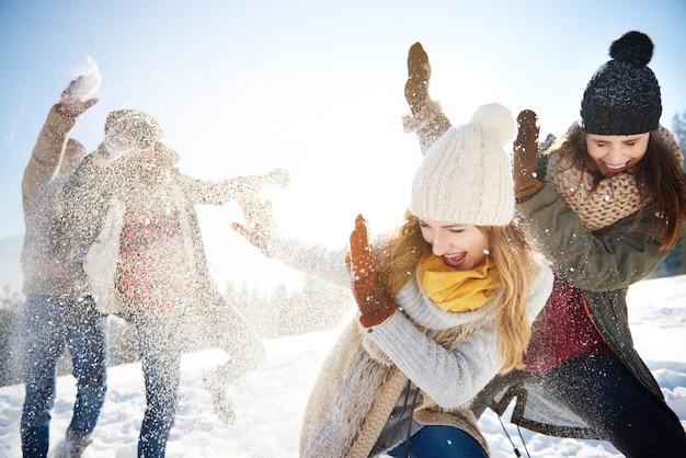 Jongens gooien sneeuwballen recht naar de meisjes