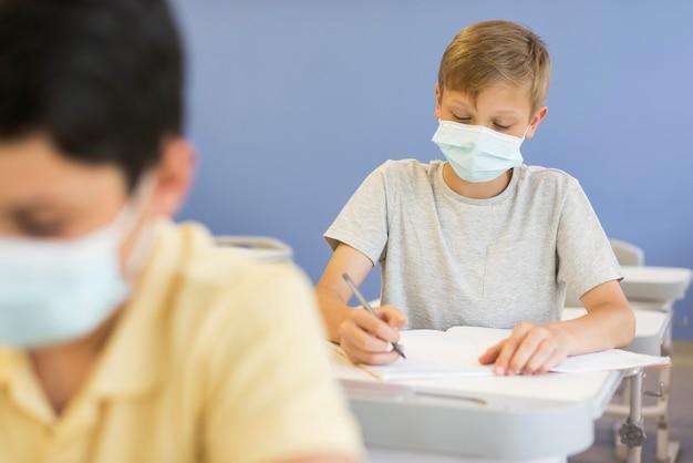 Jongens in de klas met maskers