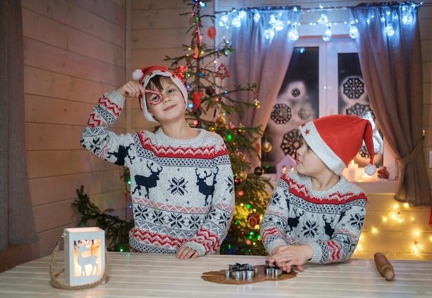 Jongens in rode petten bereiden gemberkoekjes voor de kerstvakantie