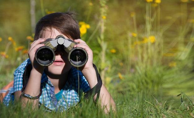 Jongens jonge onderzoeker die met verrekijkersmilieu onderzoeken in de zomertuin