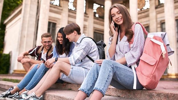 Jongens kijken iets aan de telefoon terwijl het meisje vrolijk aan het telefoneren is