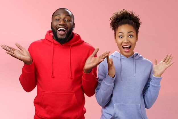 Jongens krijgen een leuke verrassing. twee aantrekkelijke zorgeloos verrast gelukkig afrikaanse man vrouw handen klappen vreugdevol begroetende gasten uitnodigen mensen uit te nodigen partij staande vriendelijke roze achtergrond