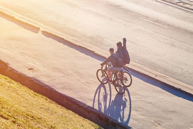 Jongens met hengels op fietsen in de zon