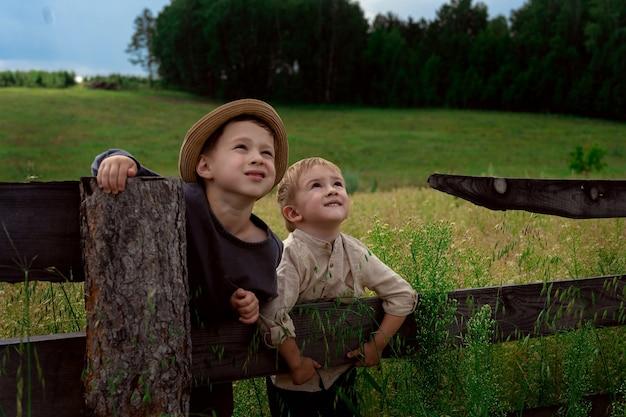 Jongens met hoed zittend op het hek