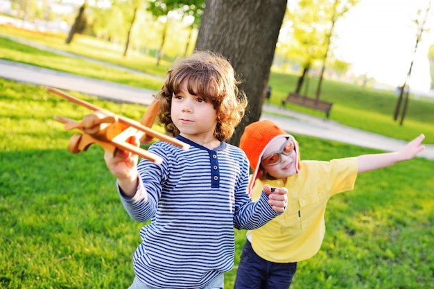 Jongens met krullend haar spelen een houten speelgoedvliegtuig in het park.