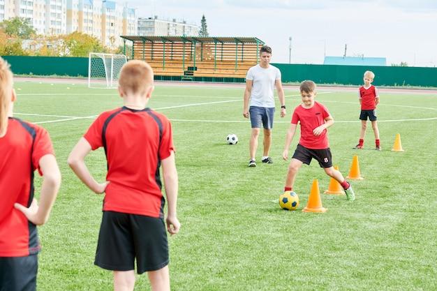 Jongens oefenen voetbal in veld