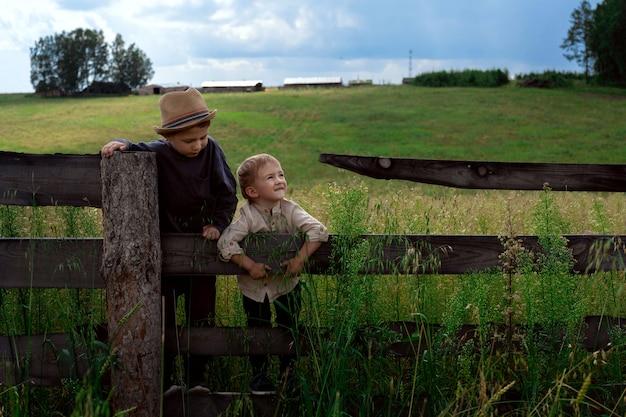 Jongens op het hek op de achtergrond van de boerderij